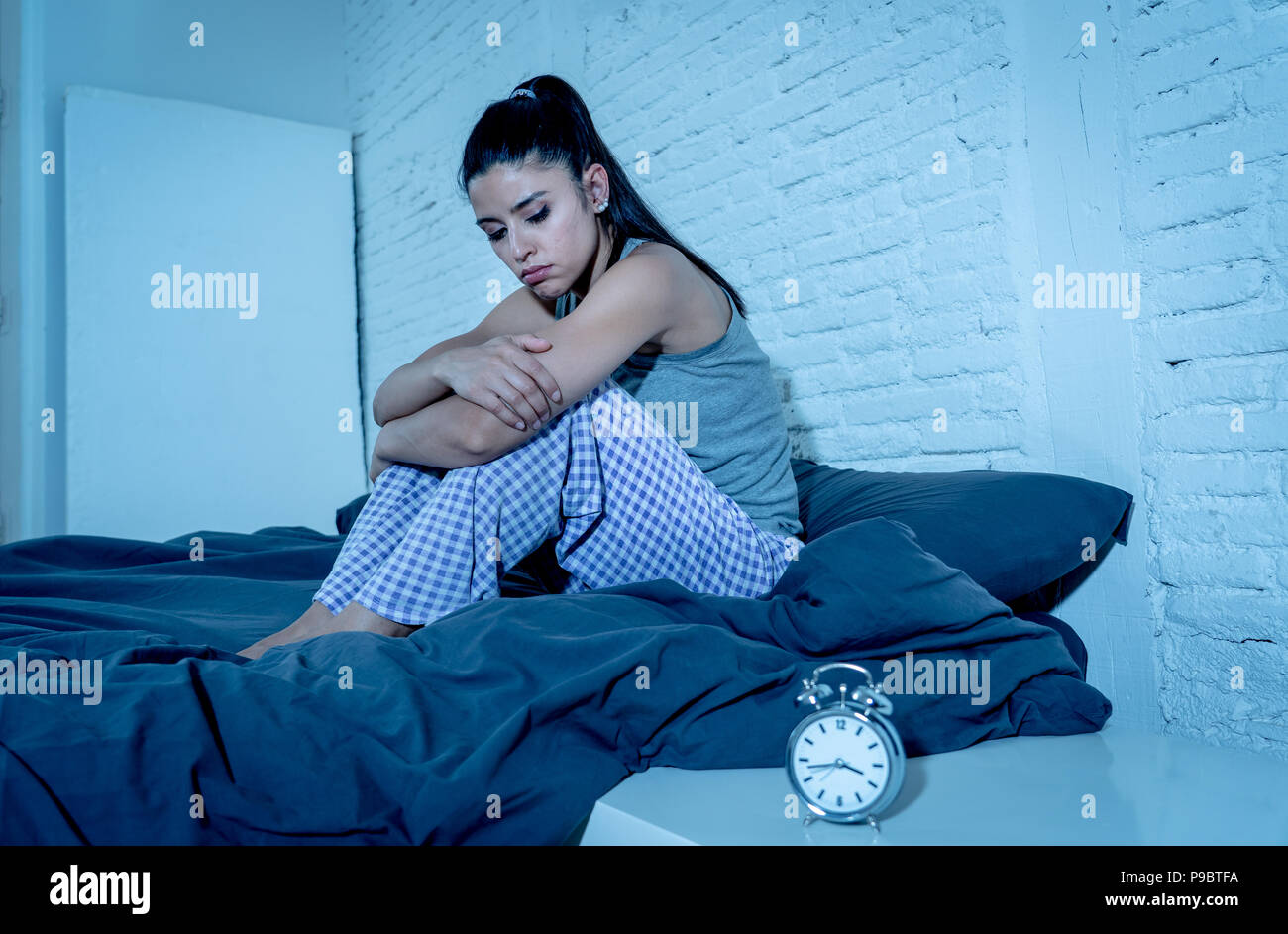 young beautiful hispanic woman at home bedroom lying in bed late at night trying to sleep suffering insomnia sleeping disorder or scared on nightmares - Stock Image