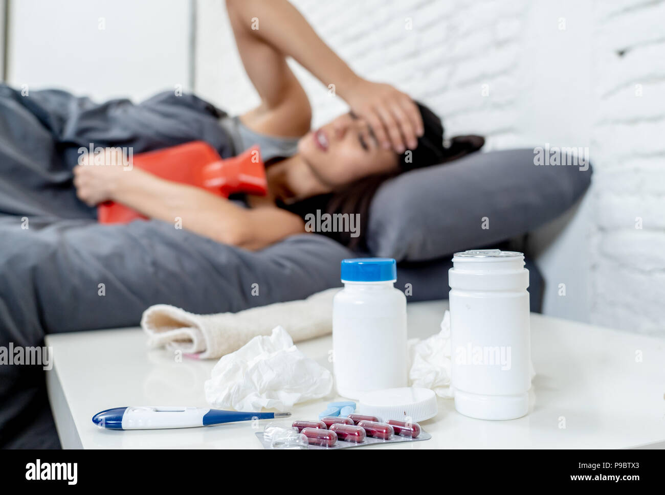 Sick hispanic woman in bed calling in sick day off from work thermometer to check temperature for fever and vitamins hot water bottle and tissues in c - Stock Image