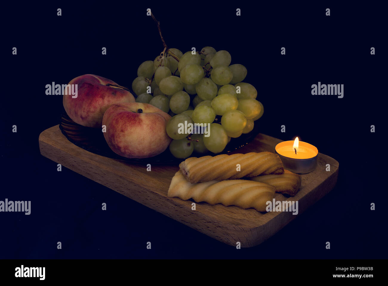 Still life from darkness. Composition with fruits, cakes and candle lighting. HD quality picture. - Stock Image