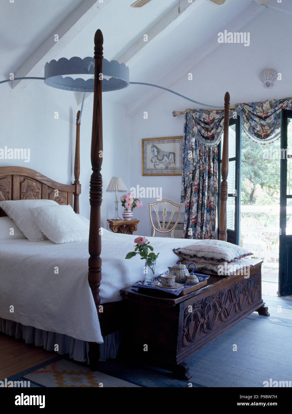 Vintage Four Poster Bed In White Spanish Bedroom With A Carved