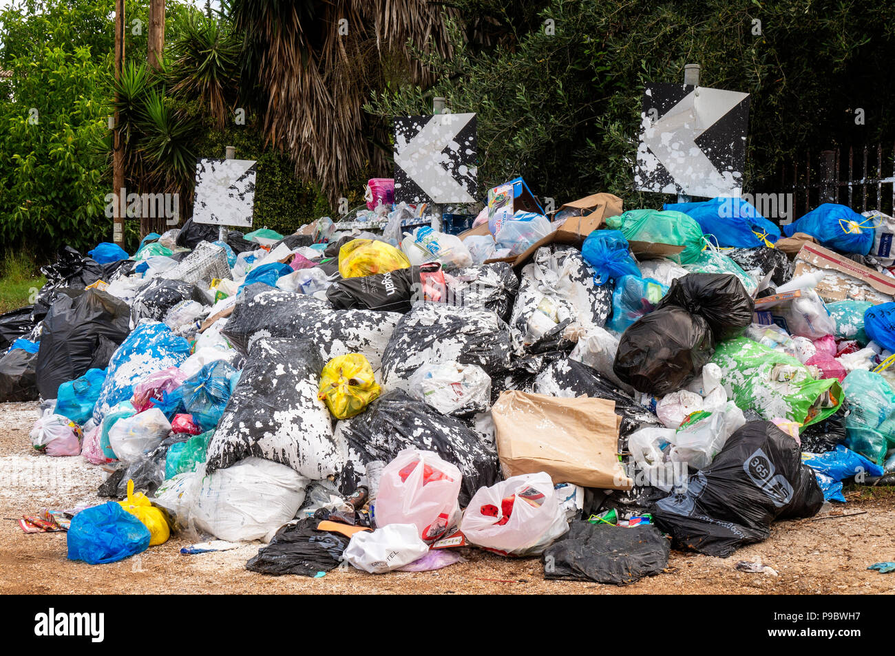 Stacked garbage bags on a street on the Greek island of Corfu Stock Photo