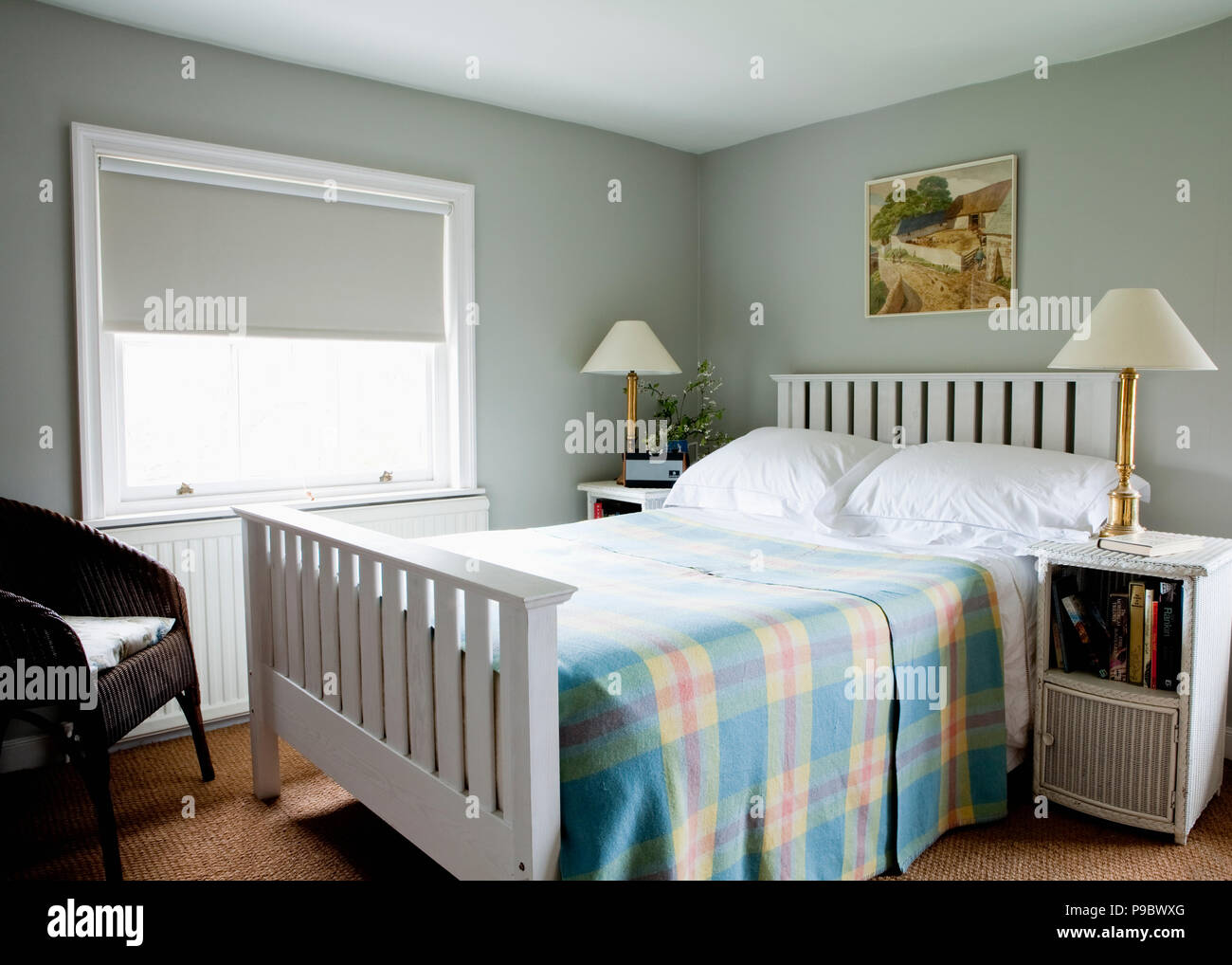 Checked Bed Cover On White Painted Bed In Pale Grey Bedroom With Pale Grey Blind On Window Stock Photo Alamy