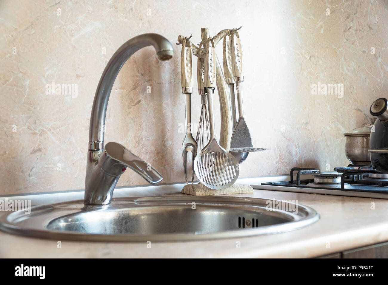 Faucet, sink and kitchen utensils. Selective focus - Stock Image