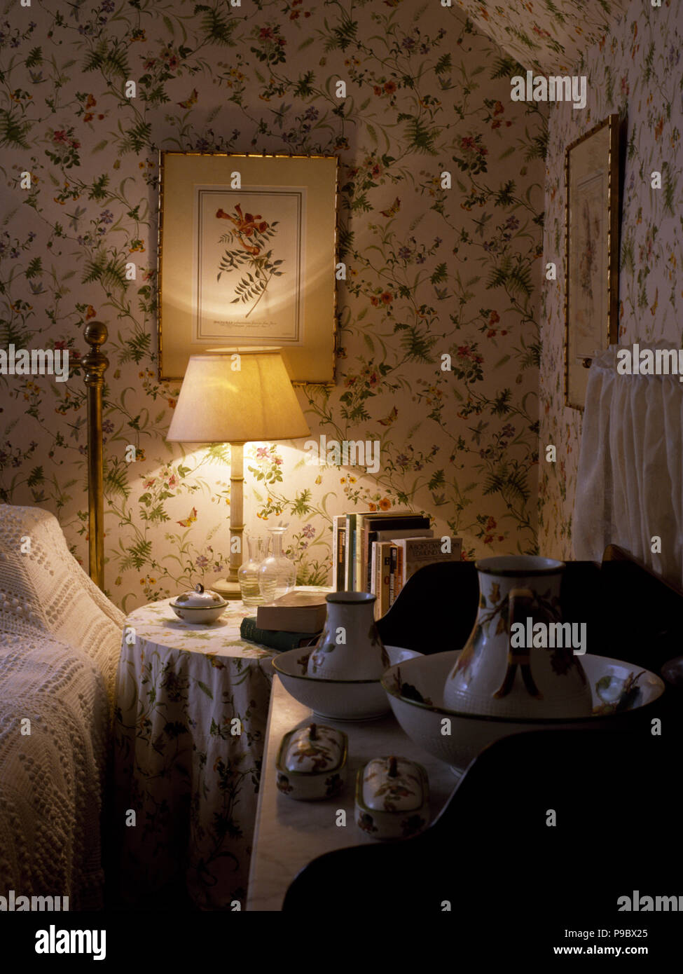 Lighted Lamp On Bedside Table In Victorian Style Bedroom With Floral  Wallpaper