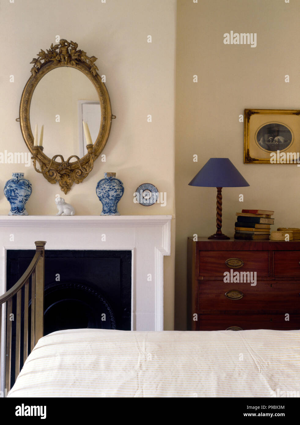 Oval Antique Mirror Above Fireplace With Blue Vases In An Economy Style  Bedroom