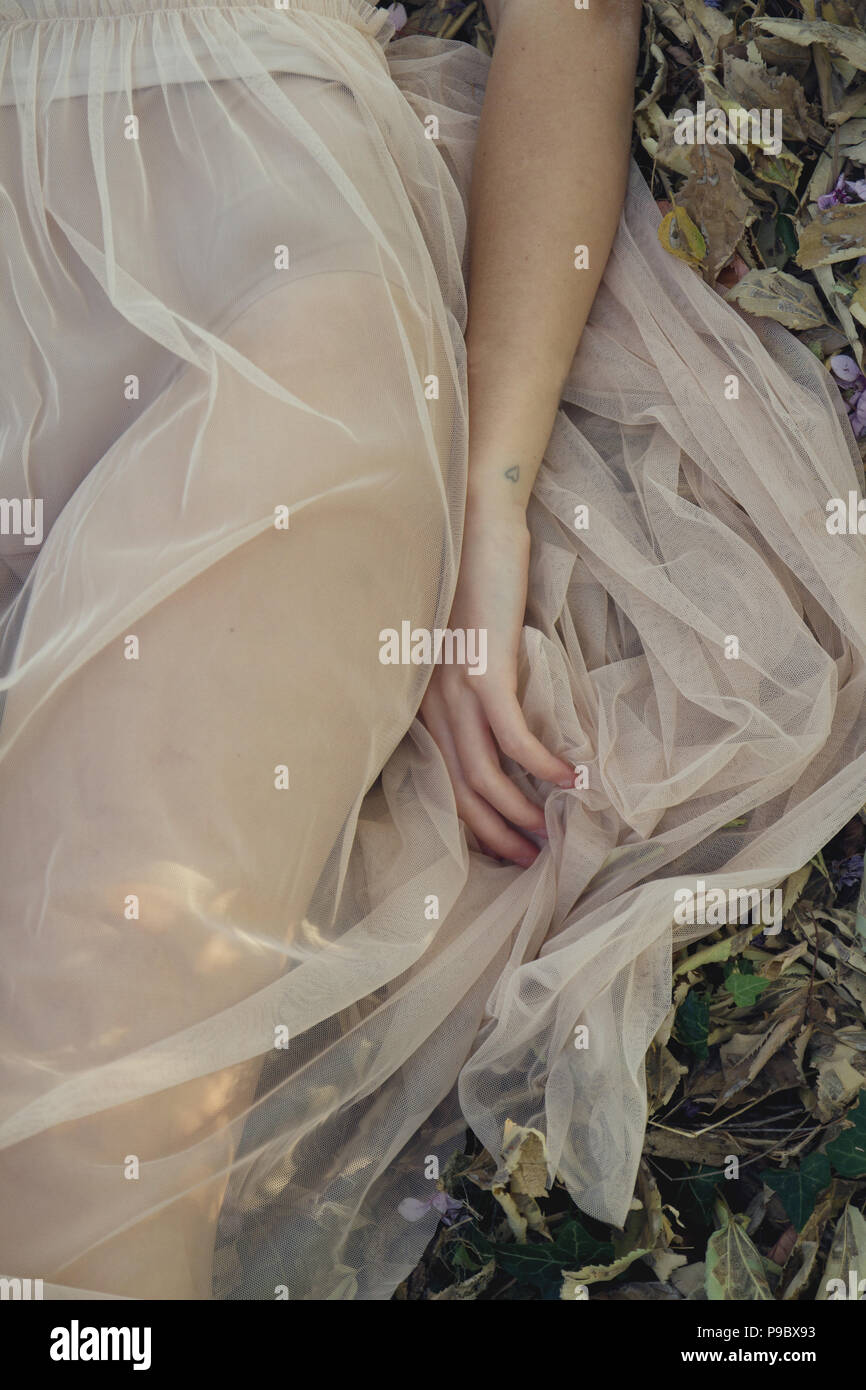 A girl in a transparent dress lying in the woods - Stock Image