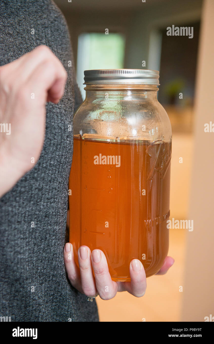 A woman holding a large jar of honey. - Stock Image