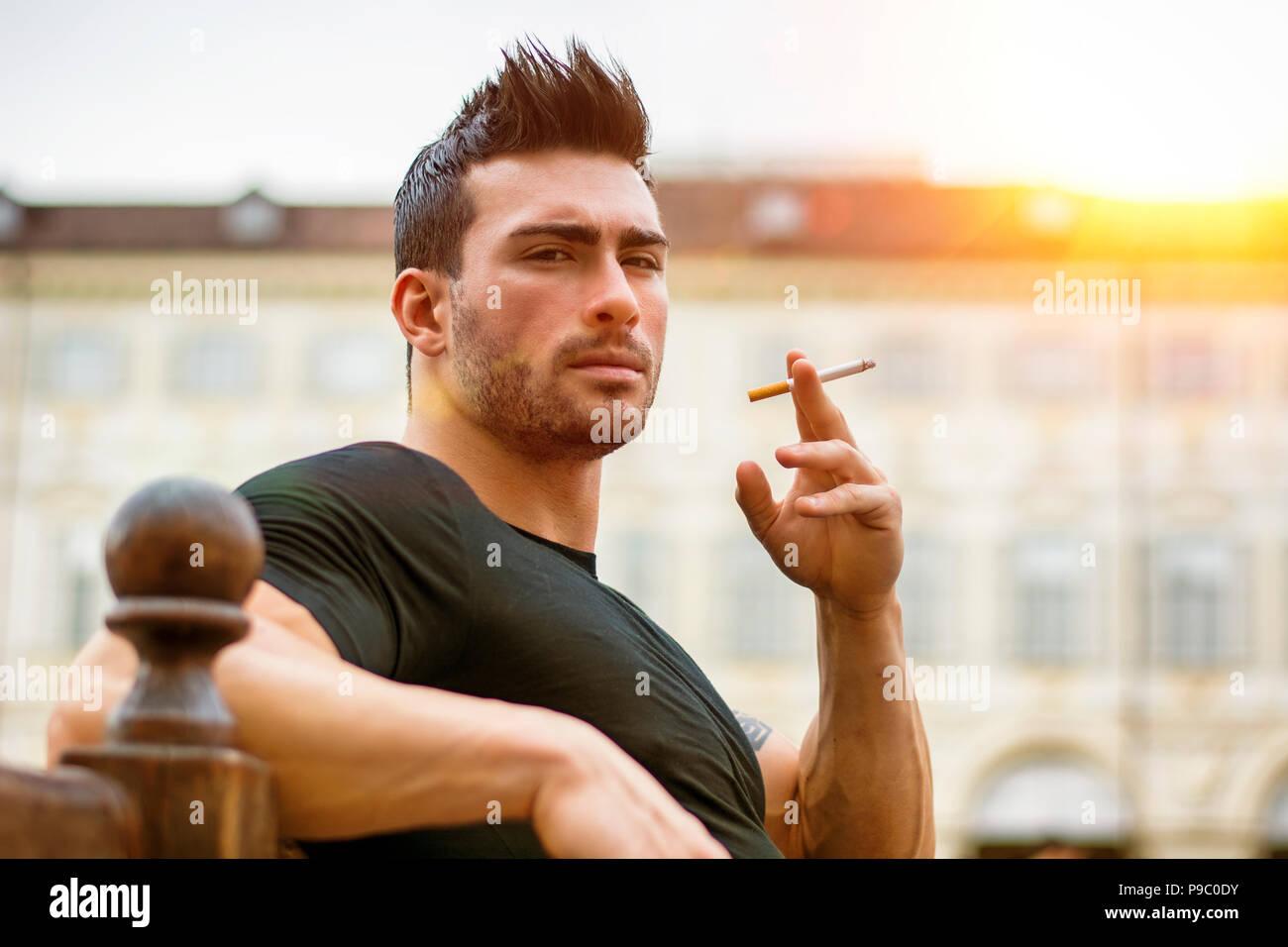 Handsome masculine man smoking - Stock Image