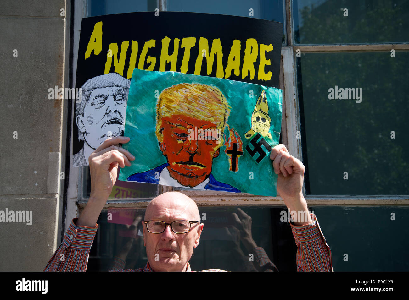 July 13th 2018.Central London. Demonstration against the visit of US President Donald Trump to England. A man holds a painting of Trump in front of an Stock Photo