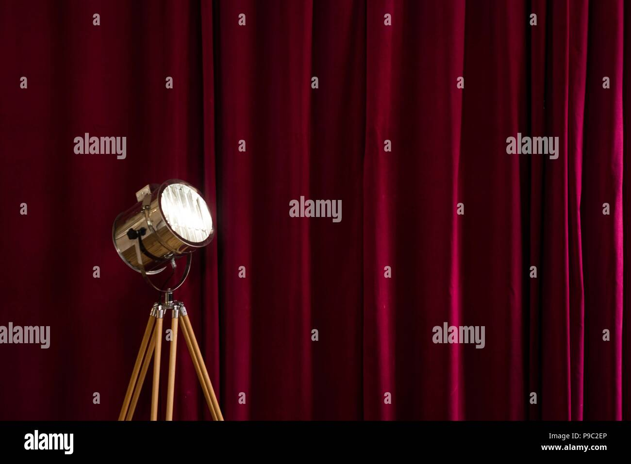 Retro studio light with a red velvet curtain background - Stock Image