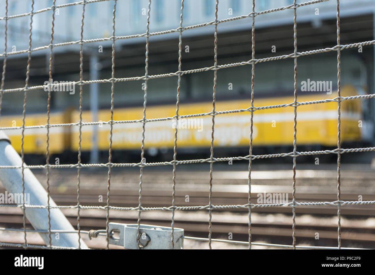 yellow train seen through grey iron fence with railtracks - Stock Image