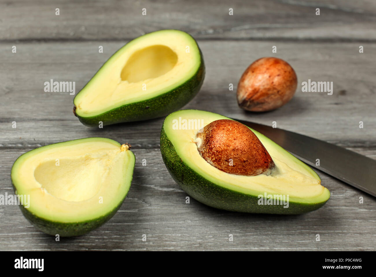Avocado Pit Cut In Half Stock Photos Avocadoseeddiagram1 Two Seeds And Chefs Knife On Gray Wood Desk