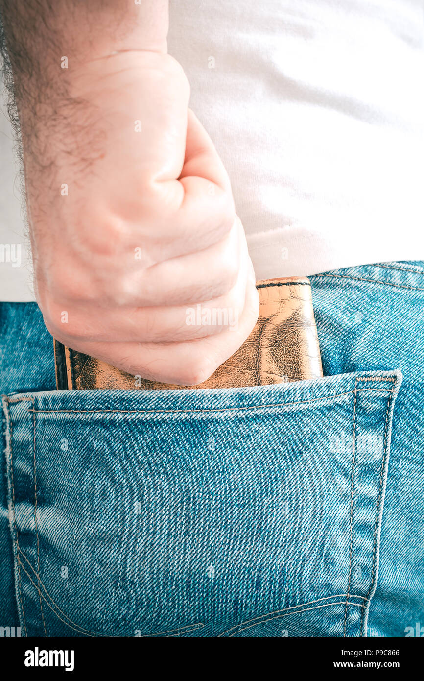 Male Hand Grabbing A Brown Leather Wallet In The Back Pocket Of A Jeans Trouser - Stock Image