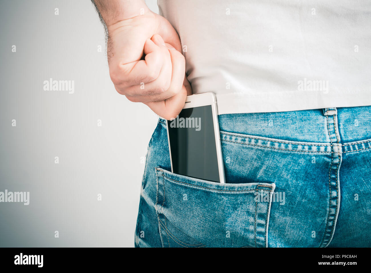 Male Hand Grabbing A Smartphone In The Left Back Pocket Of A Jeans Trouser - Stock Image