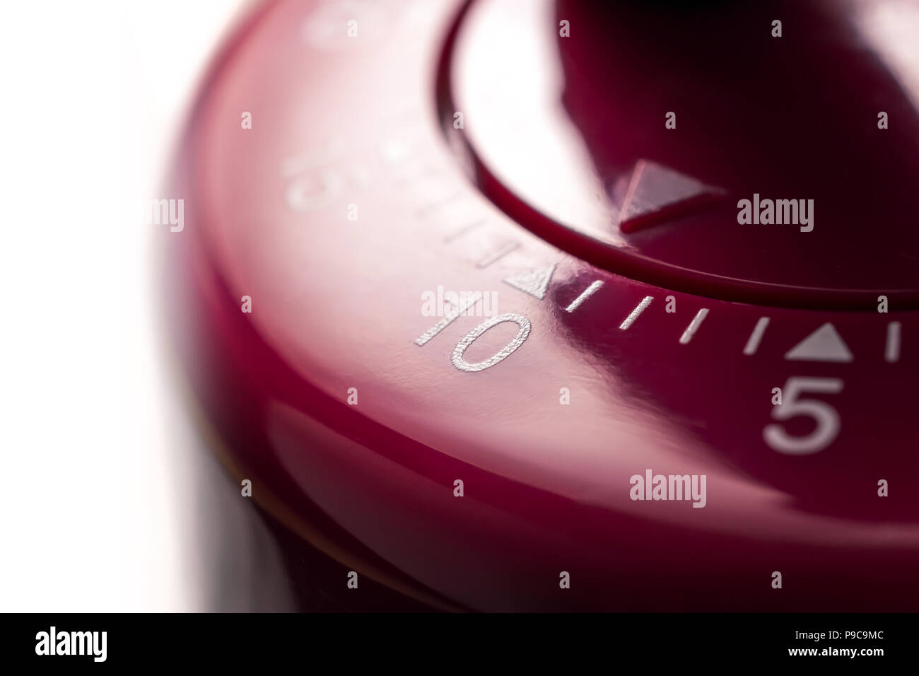 10 minutes macro of a flat red kitchen egg timer in bright atmosphere stock