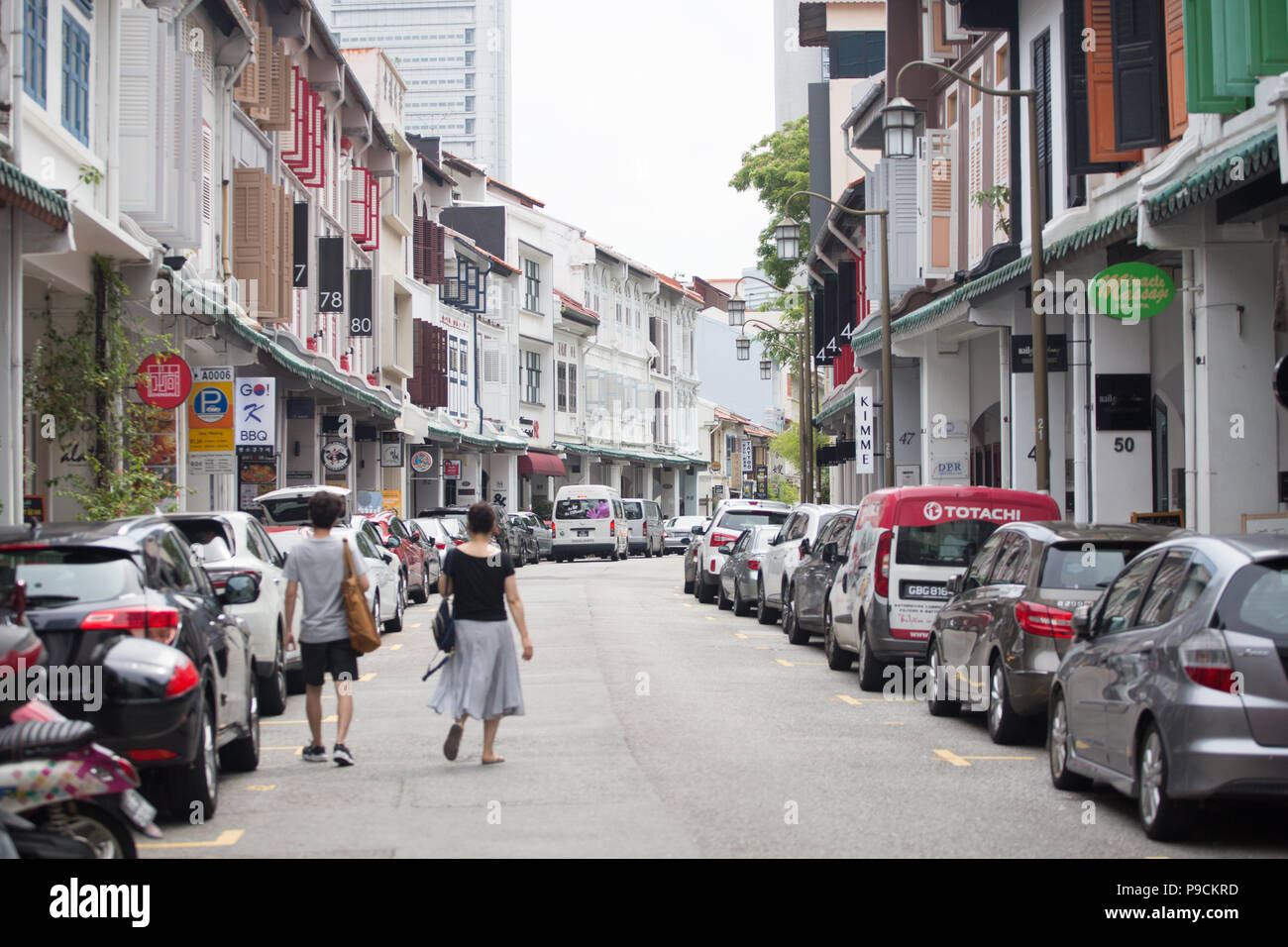 Two tourists walking on the road surrounded by shophouses, Singapore. - Stock Image