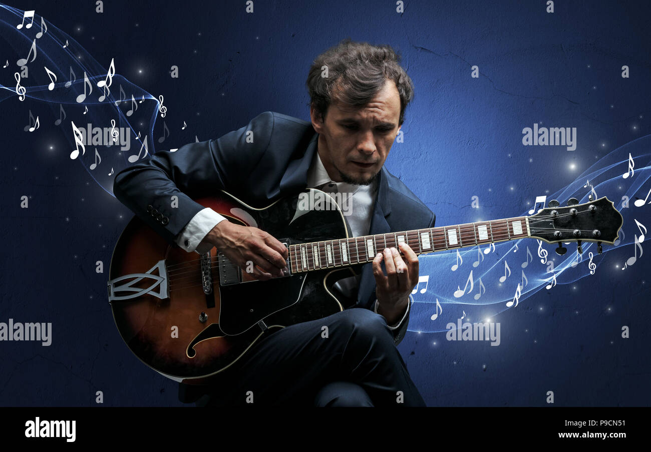 Lonely musical composer with guitar and sparkling musical notes around Stock Photo