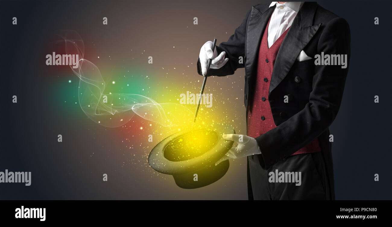 Illusionist hand starts to conjure with white glove and magic wand - Stock Image