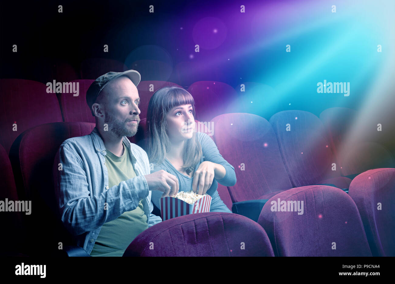 Teenager couple cuddling and watching the climax part of the movie - Stock Image