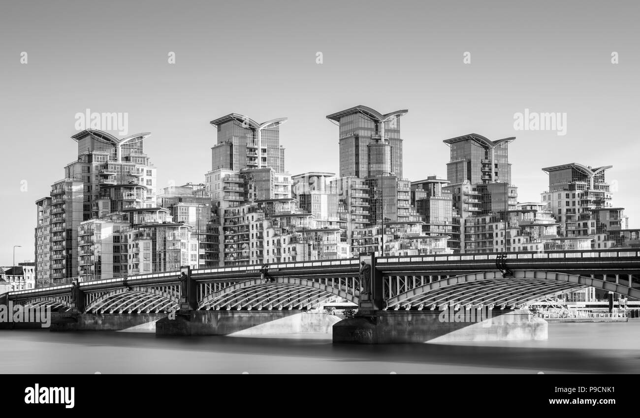 Long exposure of River Thames at Vauxhall Bridge, London, with St George Wharf accommodation and office buildings set against a cloudless sky - Stock Image