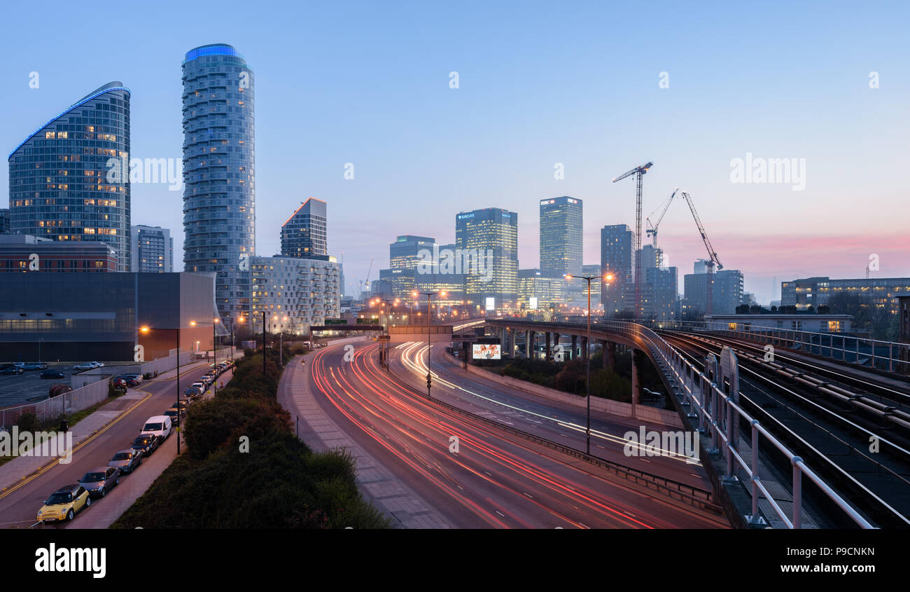 Canary Wharf and the London skyline at dusk taken from a high viewpoint at East India DLR with red light trails from cars - Stock Image