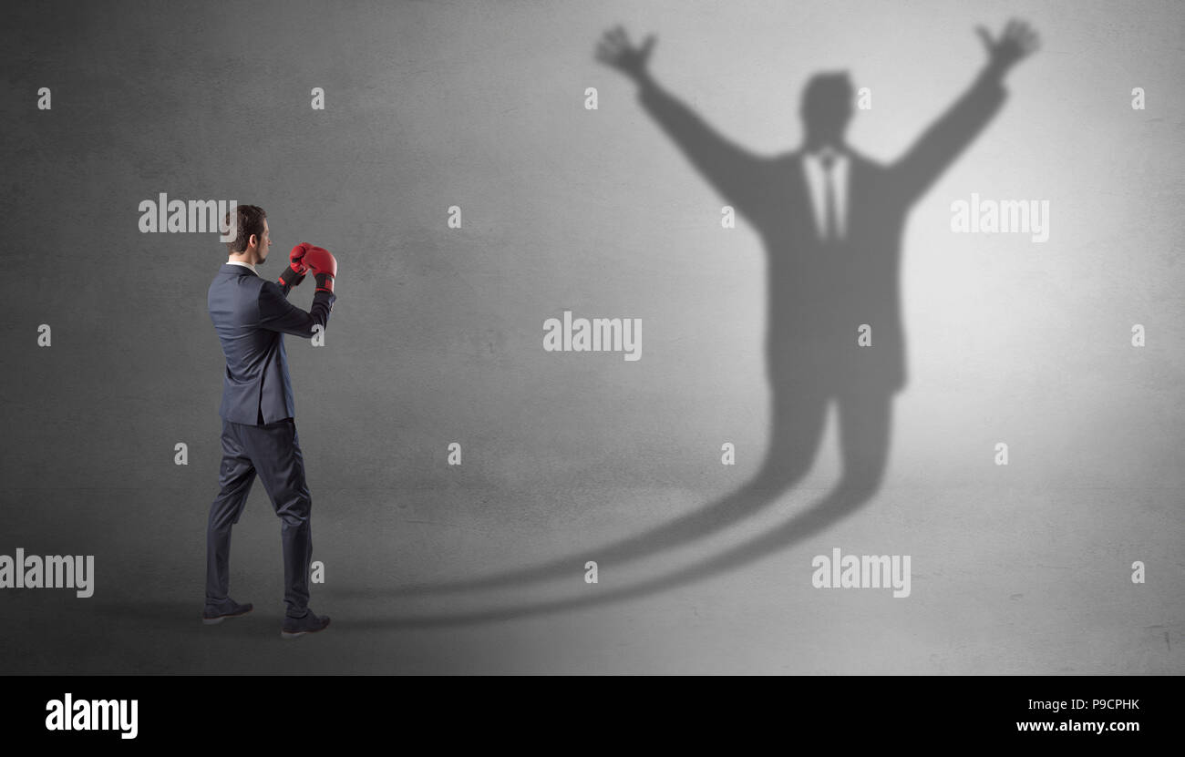 Businessman with boxing gloves fighting with disarmed businessman shadow -  Stock Image