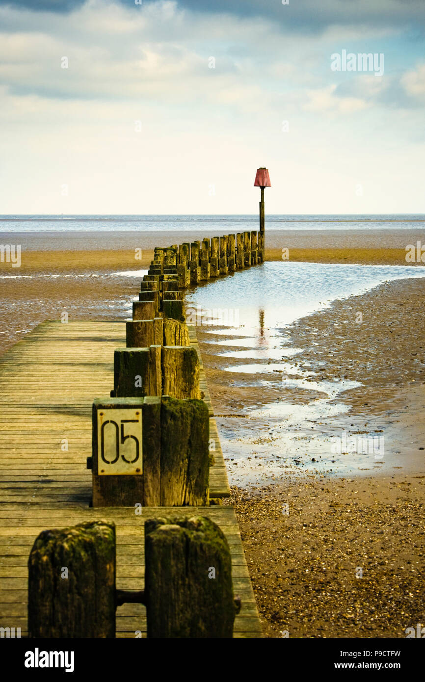 Old wooden groyne sea defence on a shingle beach looking out to sea, England, UK - Stock Image