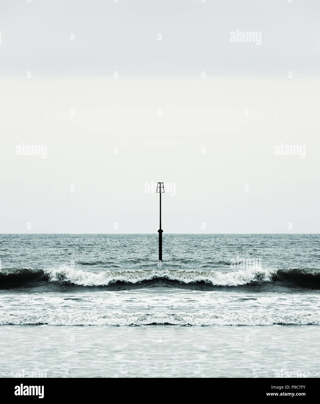 Waves and surf breaking onto a beach around a groyne beacon, England UK - symmetry concept - Stock Image