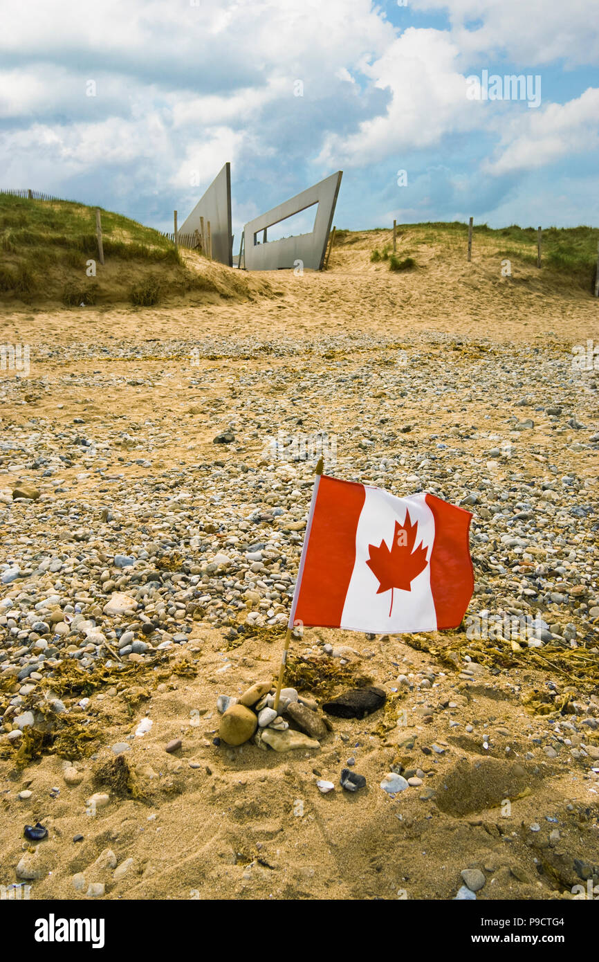 Small Canadian flag left in remembrance on Juno beach, Courseulles-sur-mer, Normandy, France, Europe - Stock Image