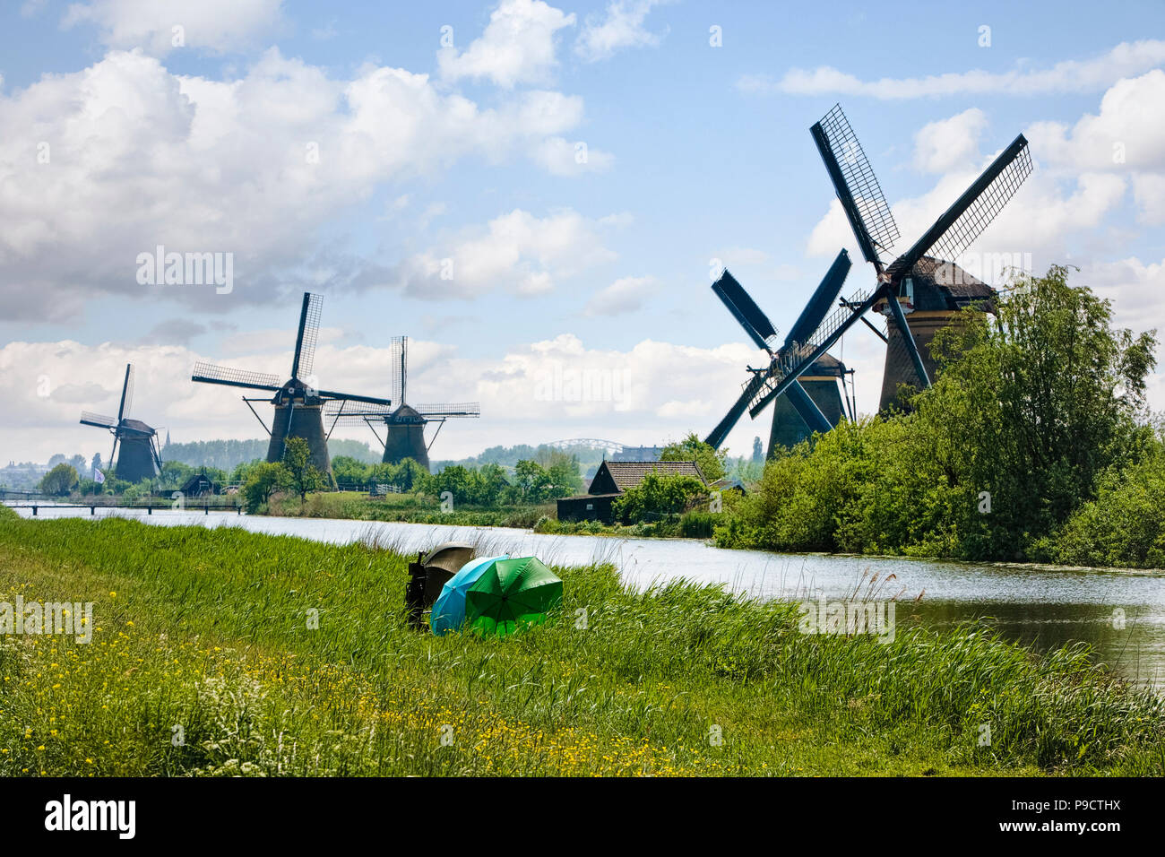 Fishermen on the riverbank beside the windmills at Kinderdijk, Netherlands, Holland, Europe - Stock Image