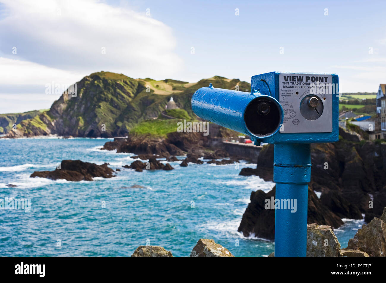 Coin operated telescope overlooking the rocky coastline at the seaside town of Ilfracombe, North Devon, England, UK - Stock Image