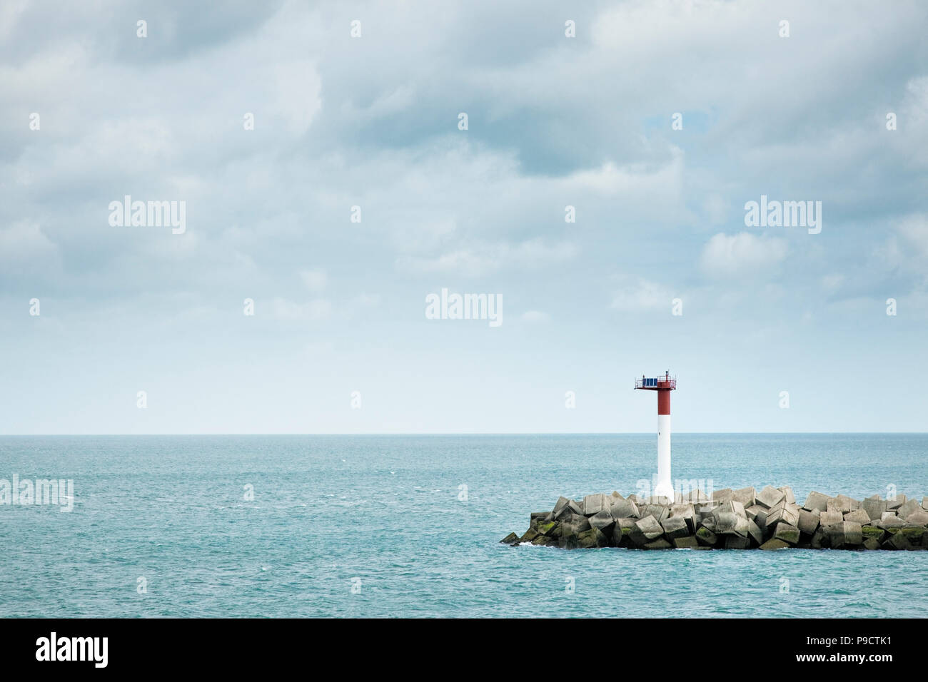 Solar powered Navigation beacon and man made harbour wall, Dunkirk, France, Europe - Stock Image