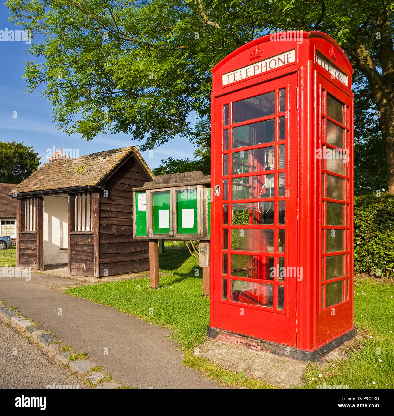Traditional British red phone box, bus shelter and village notice board scene at Lurgashall, West Sussex, England, UK - Stock Image