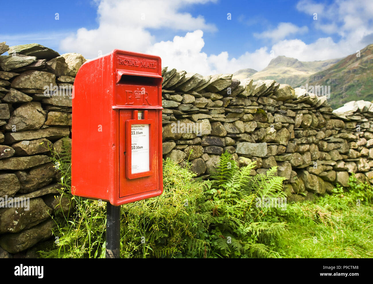 Rural red Royal Mail post letter box and dry stone wall in a remote part of the Lake District National Park, Cumbria, rural England, UK Stock Photo