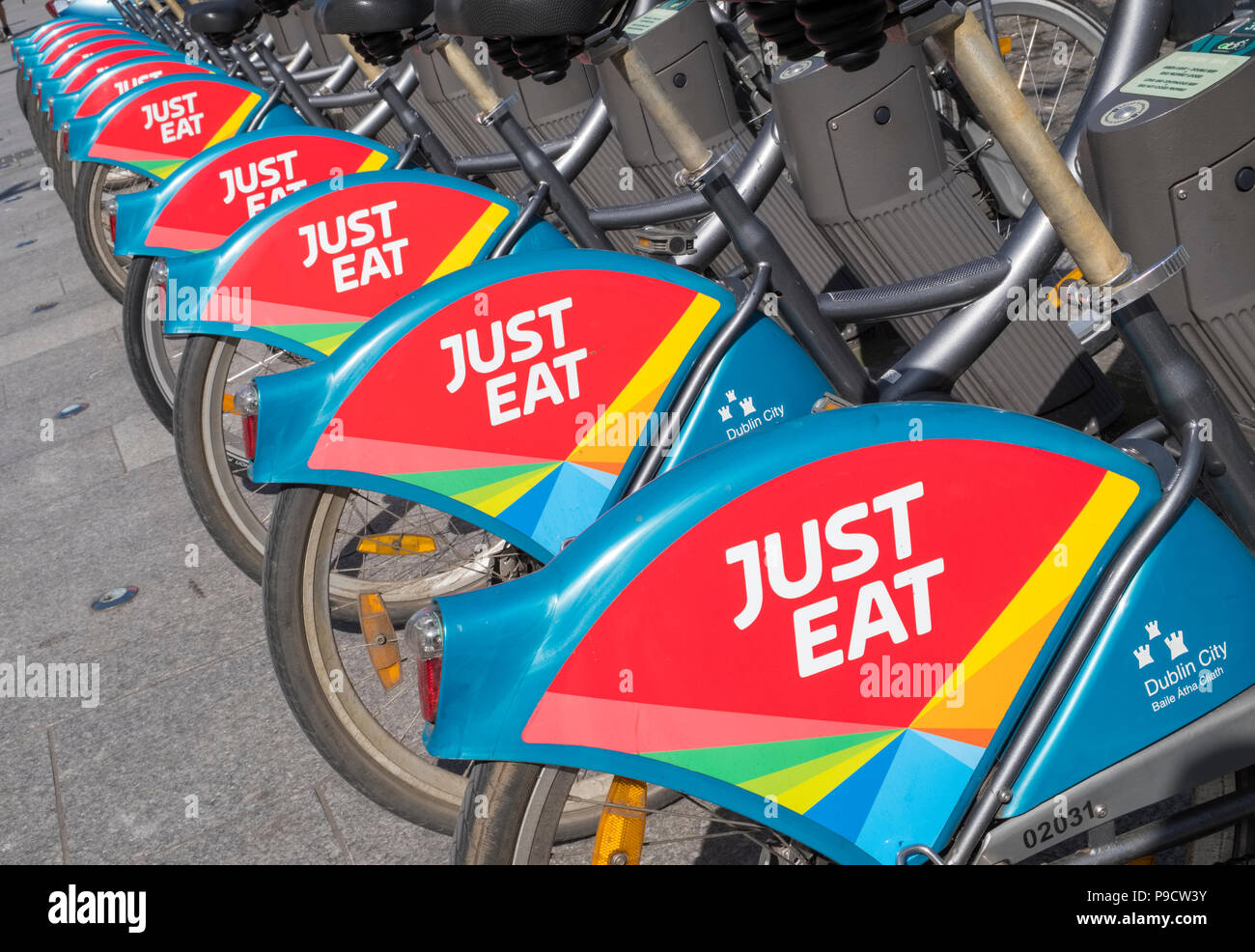 Just Eat logo sign on city bikes for hire in Dublin, Ireland, Europe - Stock Image