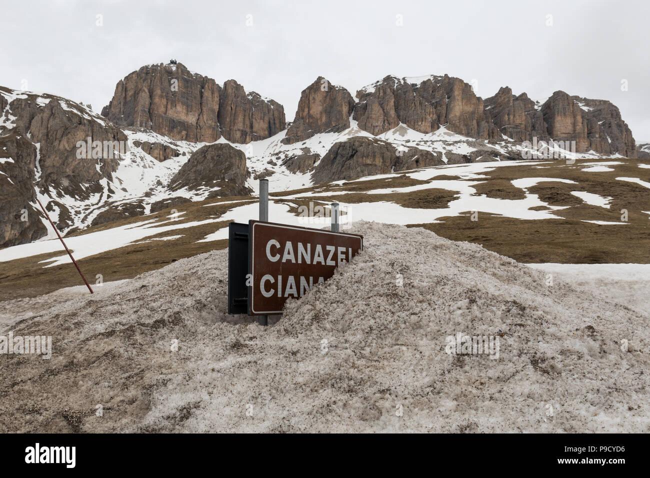 Canazei (Cianacei in Ladino language) road sign covered in snow at Passo Pordoi (Pordoi Pass), Dolomites, Italy - Stock Image