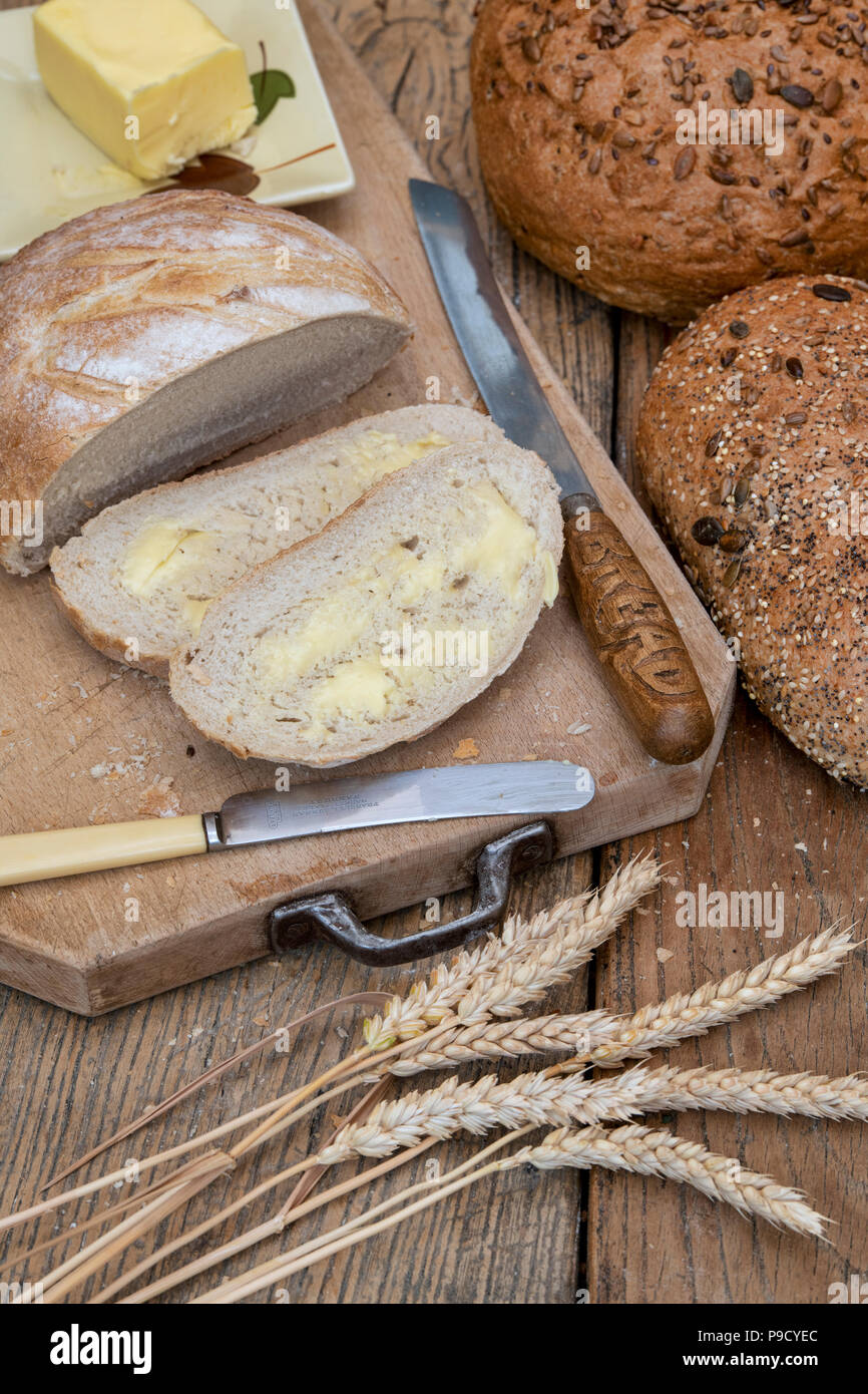 Sliced White bread with seeded loaves on a bread board with wheat and a bread knife. UK - Stock Image