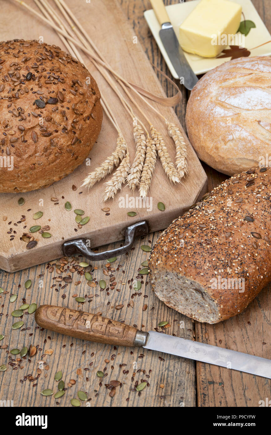 Seeded breads and a white loaf on a bread board with wheat and a bread knife. UK - Stock Image
