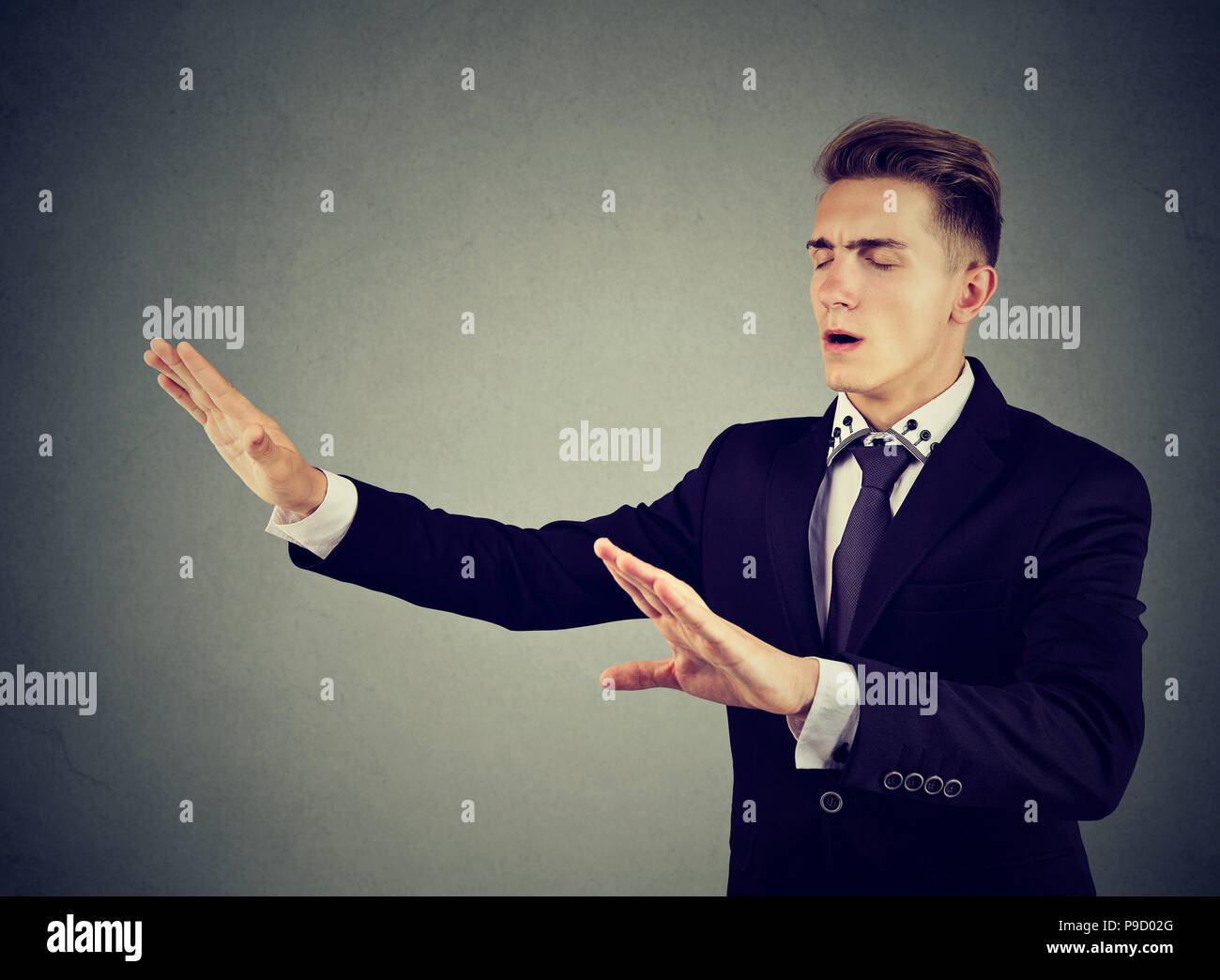 Young blindfolded man in elegant suit outstretching hands and searching in darkness on gray background - Stock Image