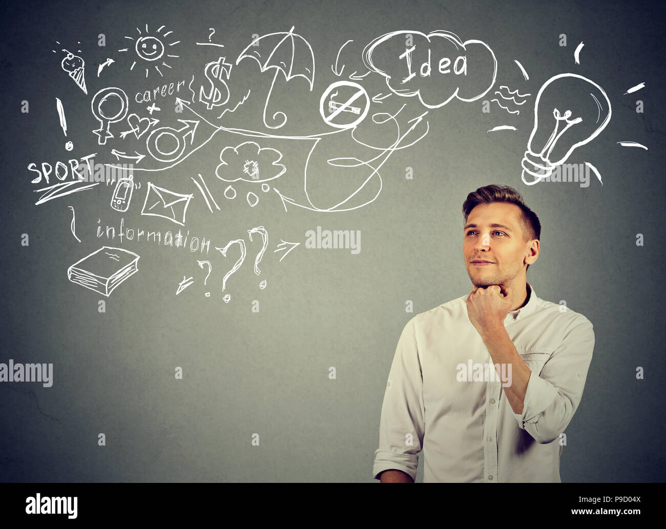 Smart inspired man looking away while making business plan and thinking on new idea against gray background - Stock Image