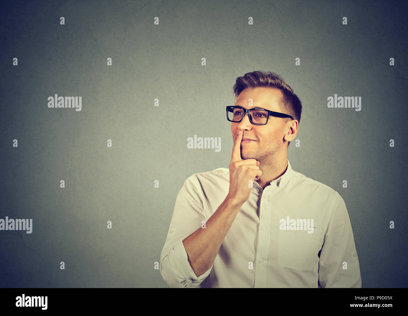 Adult handsome man touching lips and looking away in inspiration while creating new plan and daydreaming - Stock Image