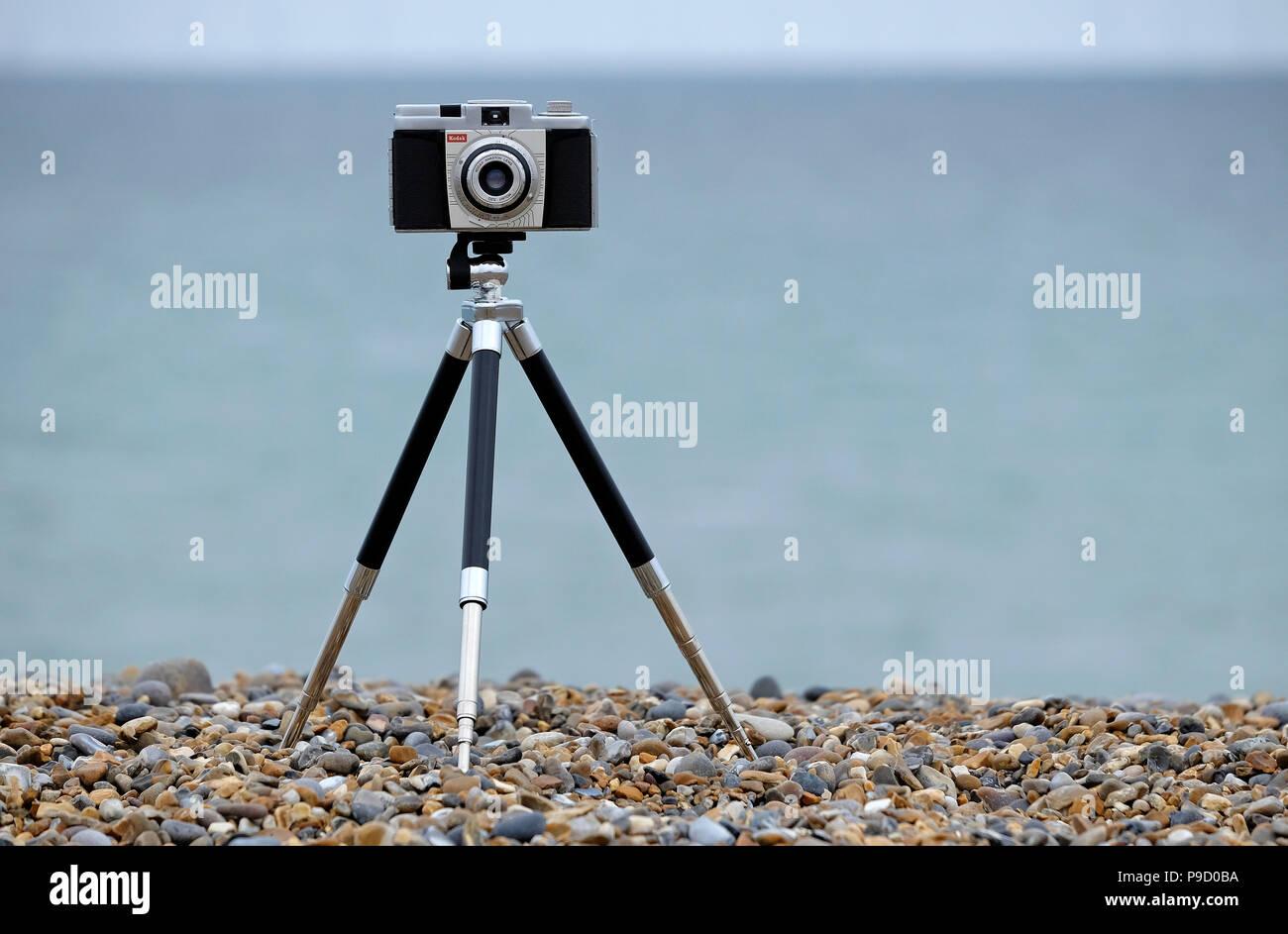 vintage retro film camera and metal telescopic tripod on shingle beach, north norfolk, england Stock Photo