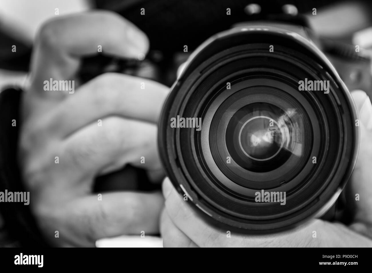 Close-up black and white shot of crop hands holding professional photo camera and taking pictures - Stock Image