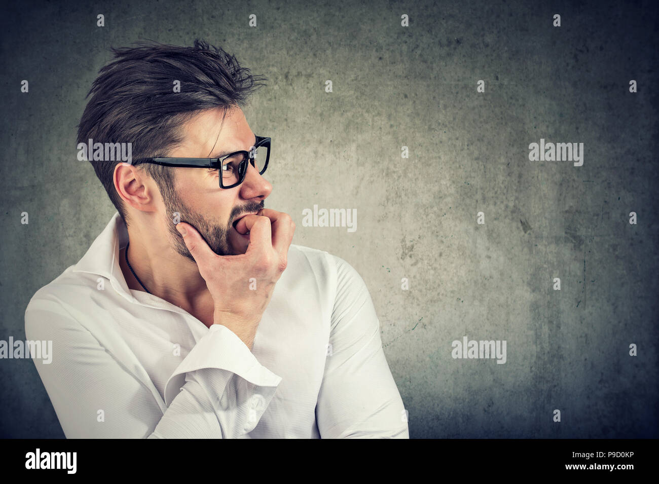 Adult bearded man having panic and phobia looking away while biting nails in anxiety on gray background - Stock Image