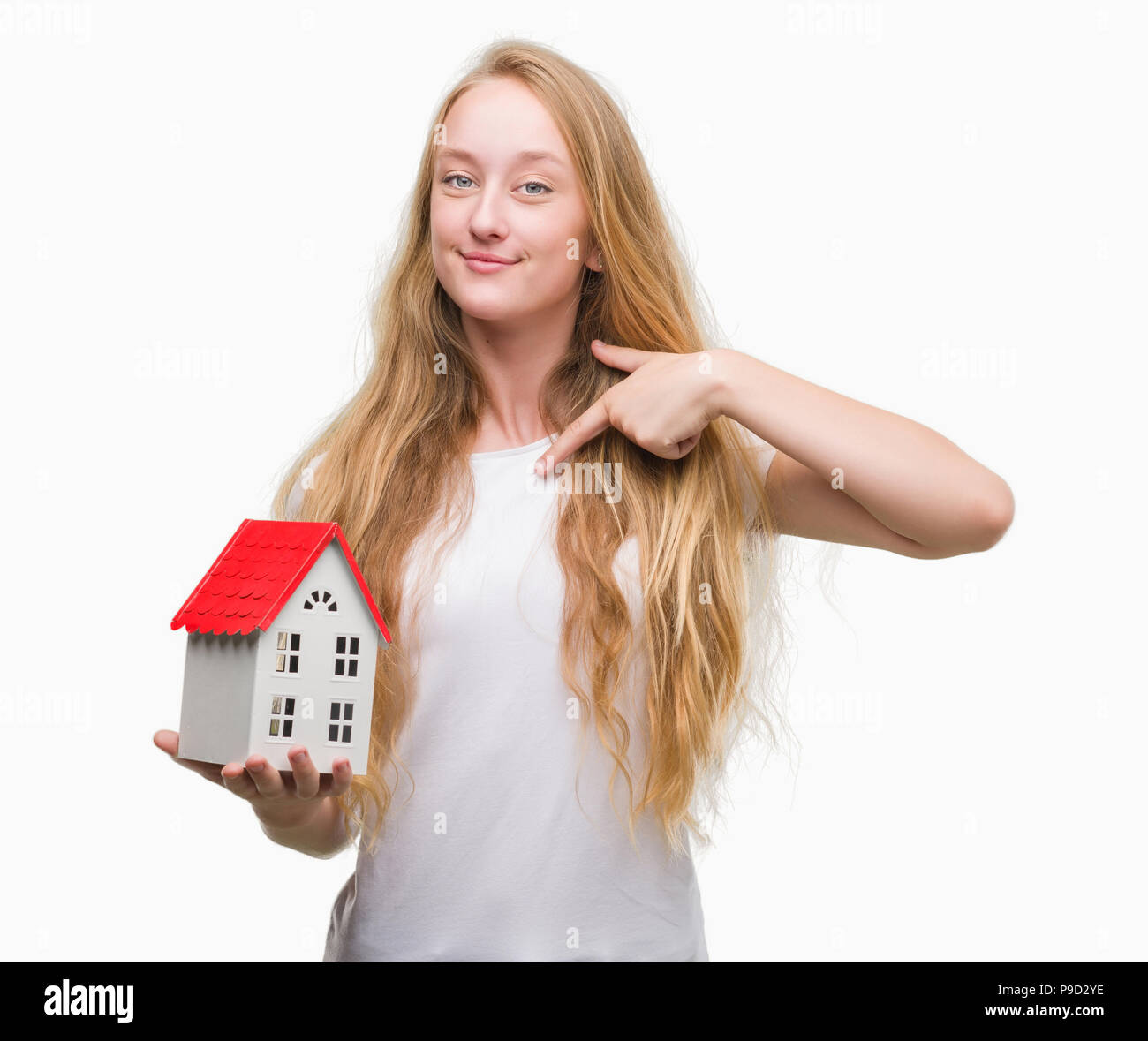 Blonde teenager woman holding family house with surprise face pointing finger to himself - Stock Image