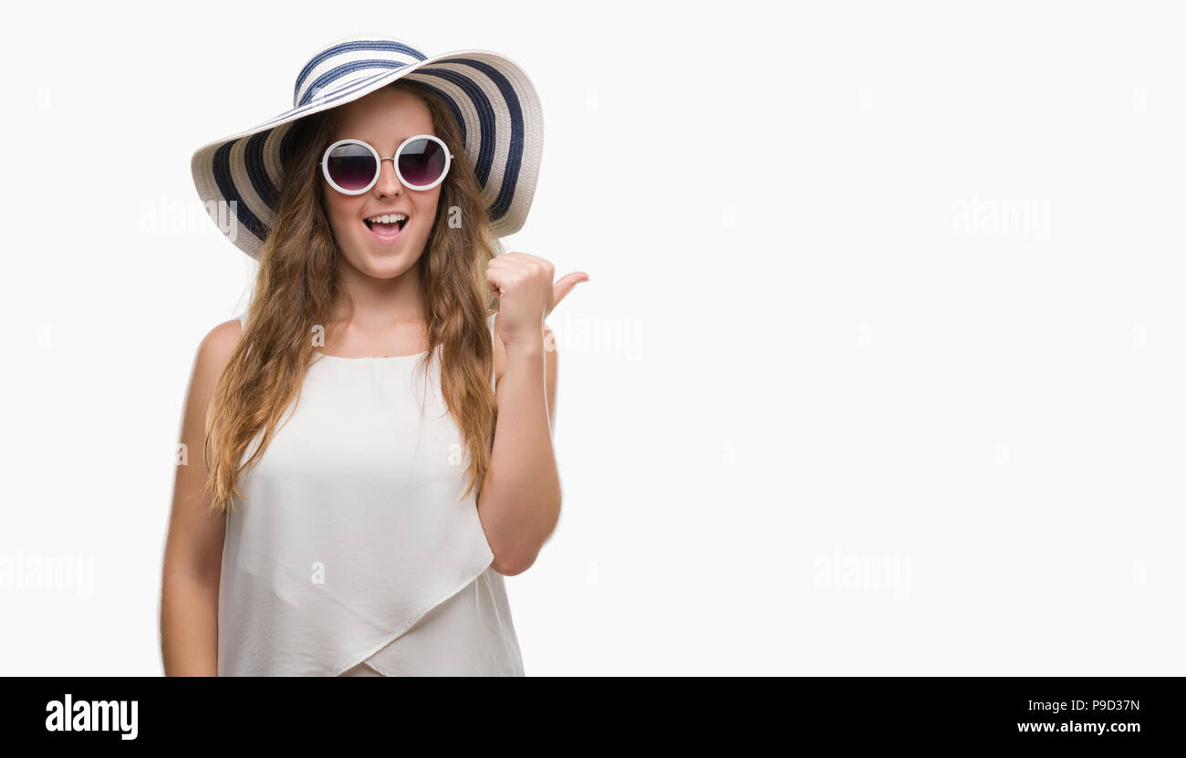 Young blonde woman wearing sunglasses and summer hat pointing and showing with thumb up to the side with happy face smiling - Stock Image