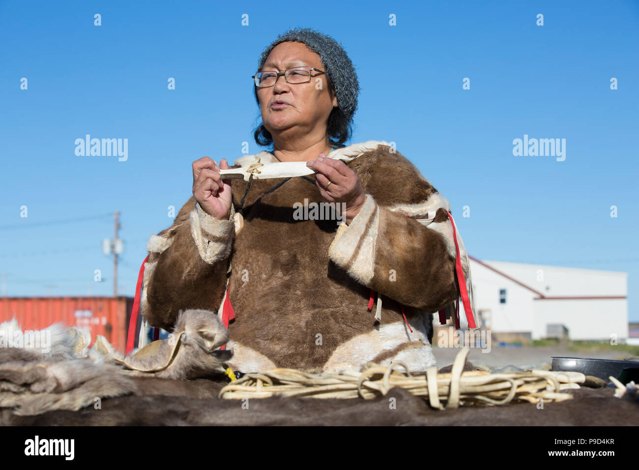 Canada, Nunavut, Hudson Bay, Kivalliq, Arviat, local woman demonstrates historic tools used by inuit. - Stock Image