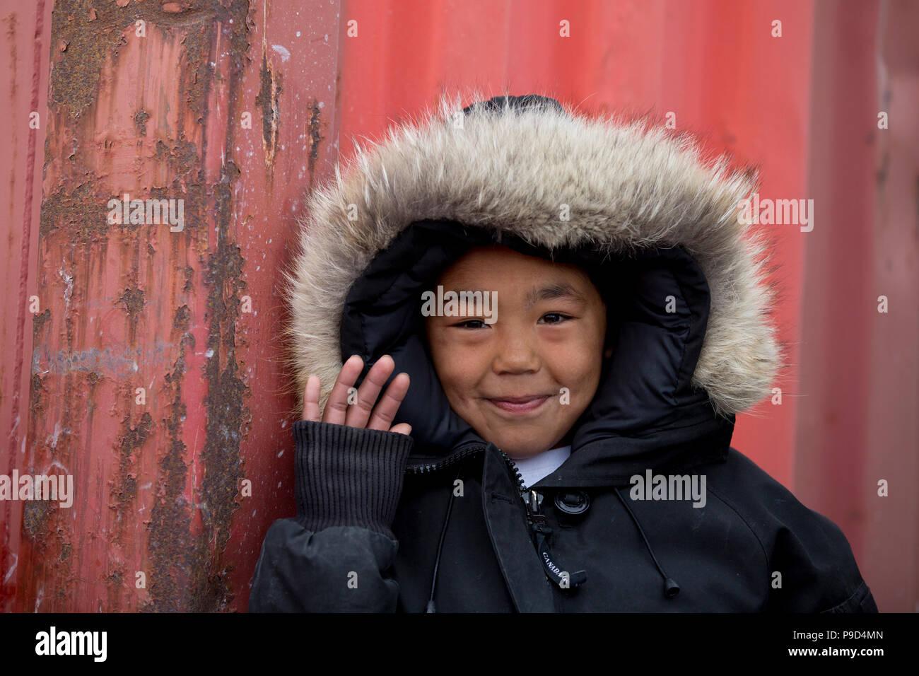 Canada, Nunavut, western shore of Hudson Bay, Kivalliq Region, Arviat. Young boy waving. Stock Photo