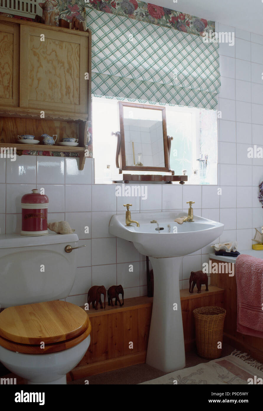 Picture of: Wooden Cabinet Above Toilet With Wooden Seat In Small Bathroom With Green Checked Blind Above Pedestal Basin Stock Photo Alamy
