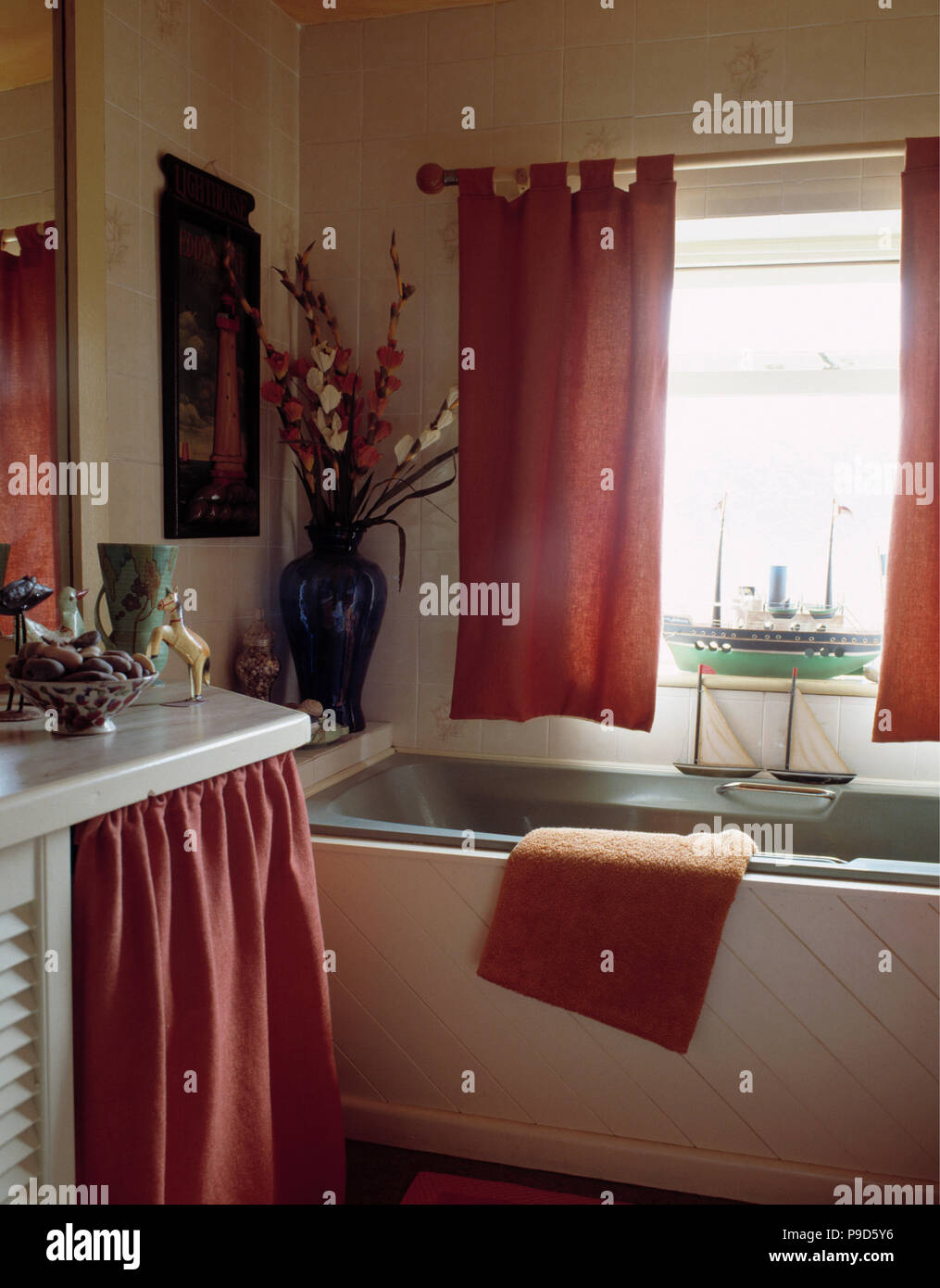Pink Curtains On Window Above Grey Bath In Cottage Bathroom With Pink Curtain On Vanity Unit Stock Photo Alamy